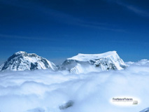 The peaks of Huascaran and Hualcan mountains in Peru, seen from above puffy white clouds.