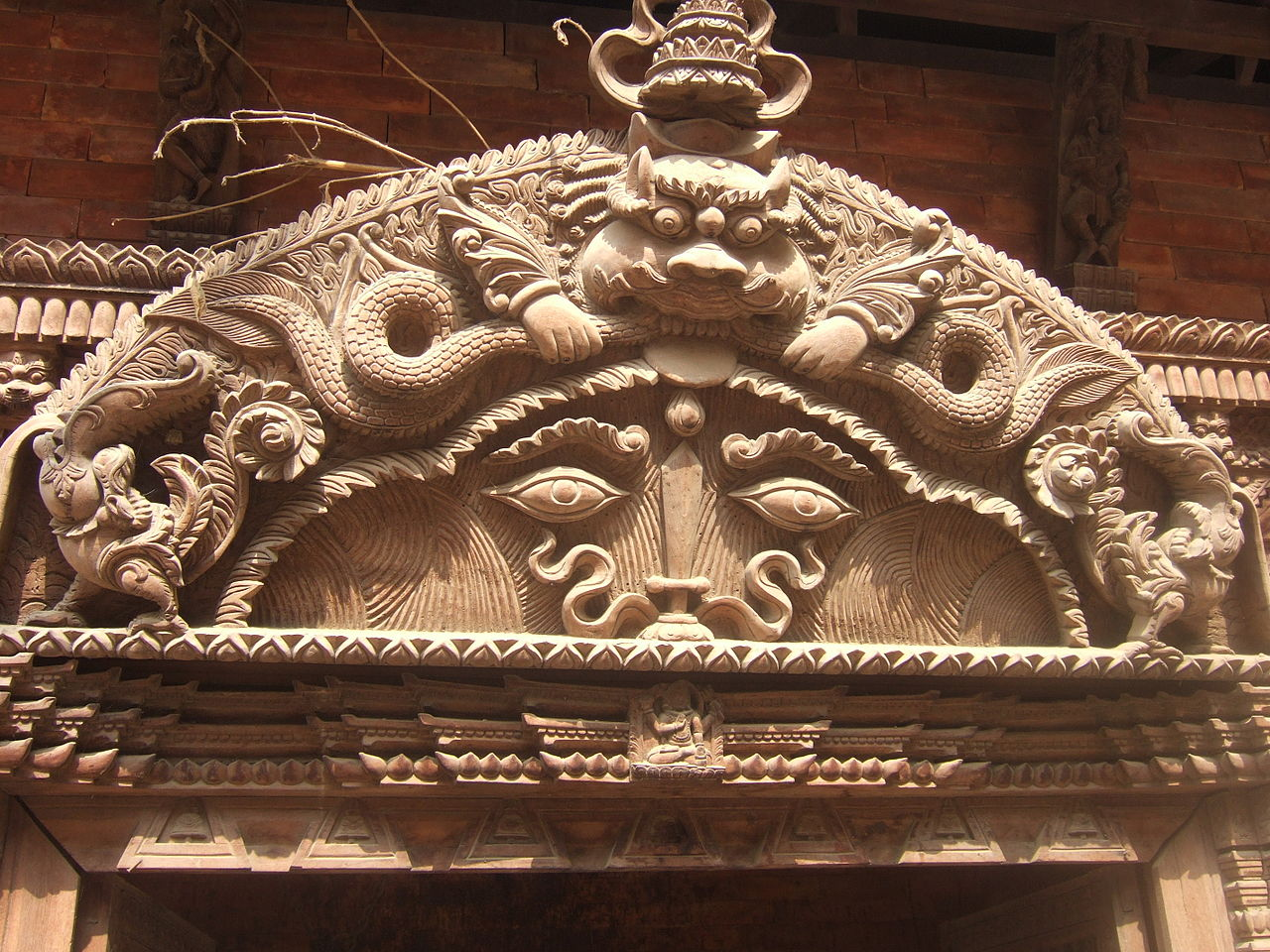Kirtimukha on top of arch above entrance to Hindu temple