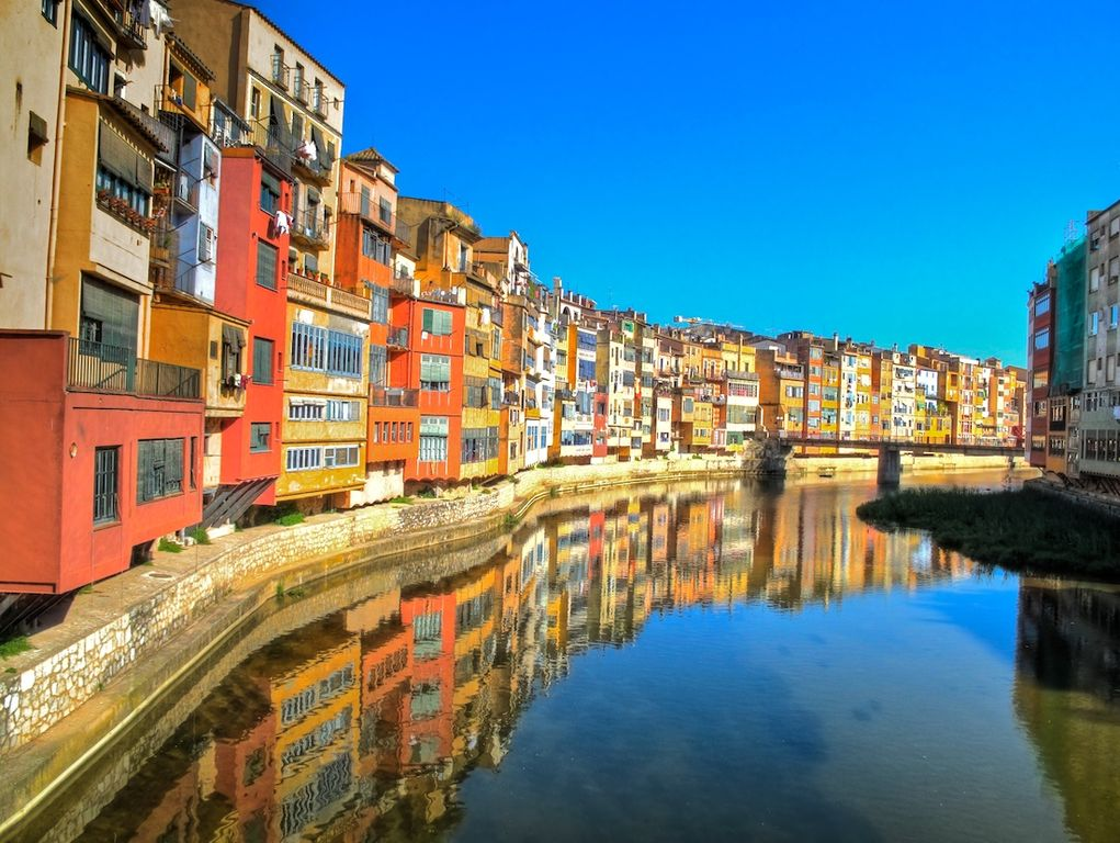 Colorful houses cling to the banks of Riu Onyar in the oldest section of Girona, Catalonia, Spain