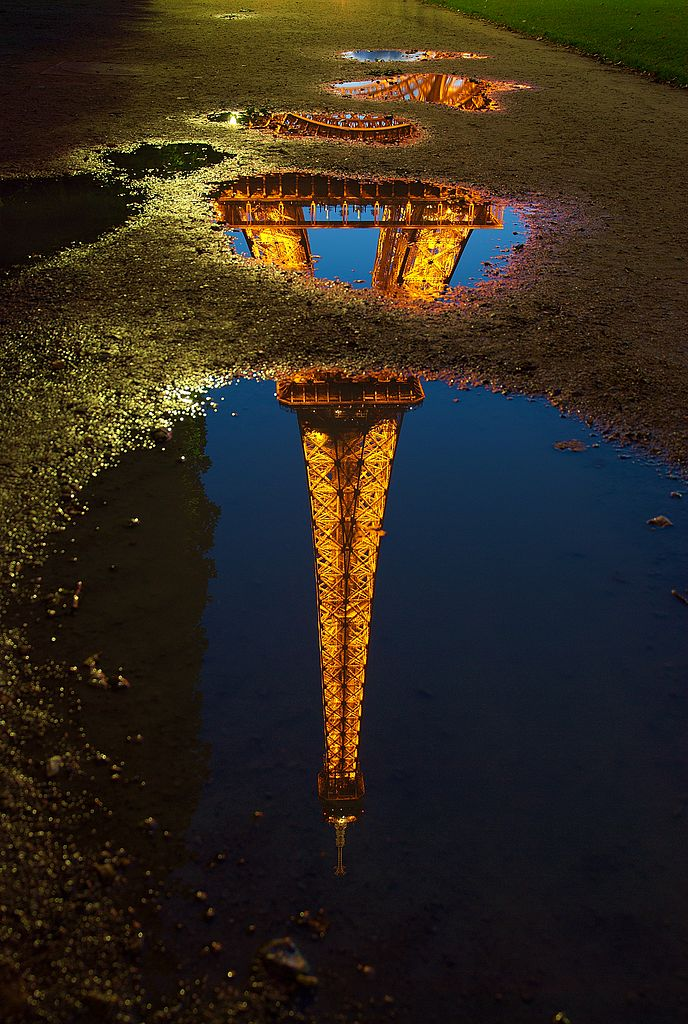 Reflection of the Eiffel tower in a water puddle. Paris, France.