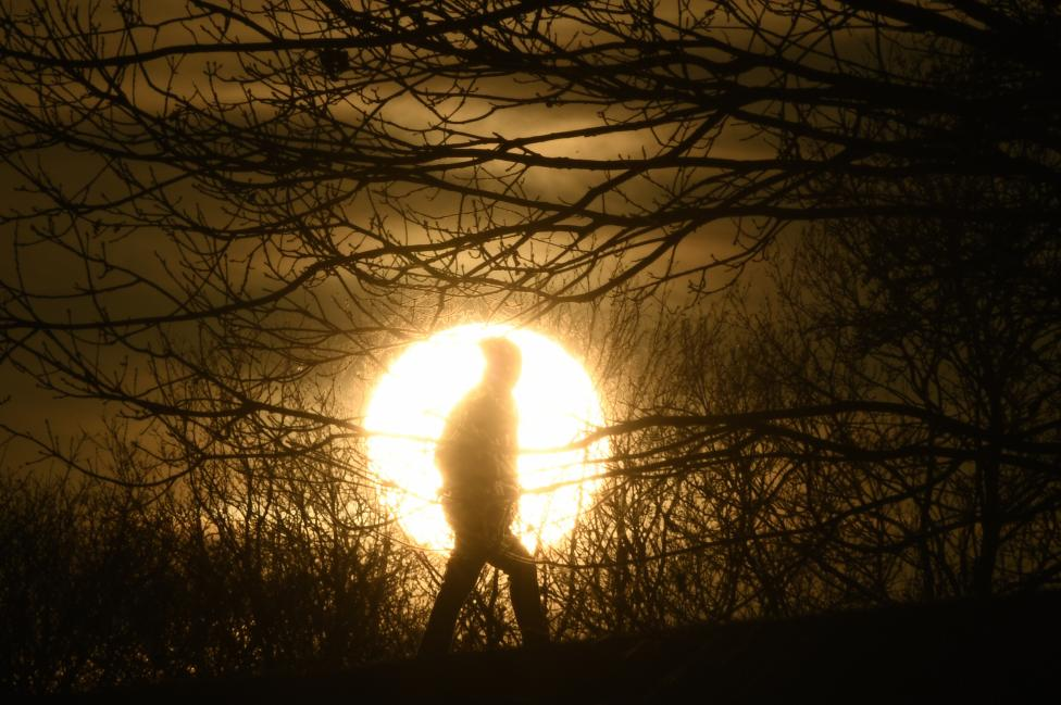 A walker passes in front of the setting sun on Primrose Hill in London